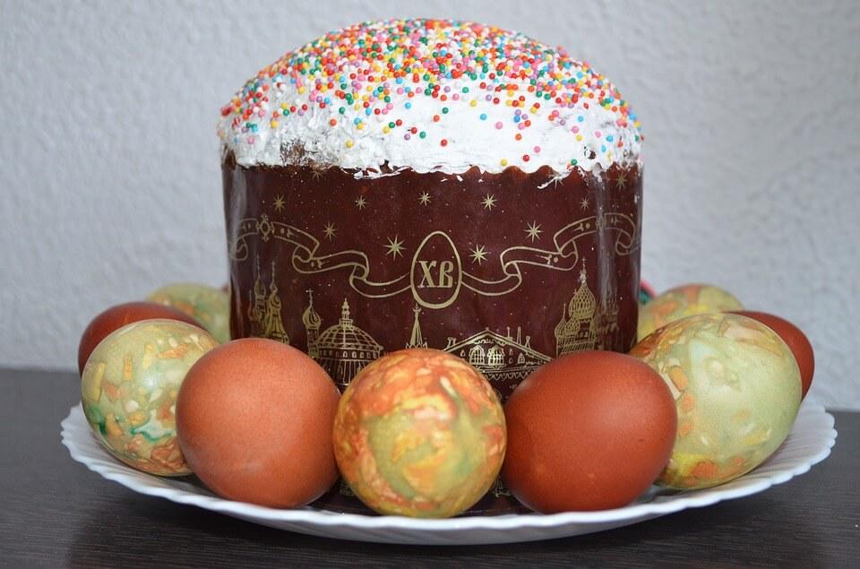 На фото изображен пасхальный кулич и крашенные яйца.