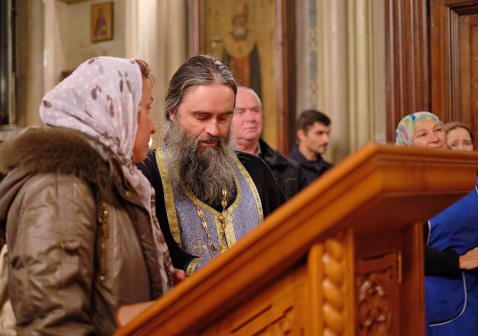 На фото изображено, как женщина исповедуется в церкви.
