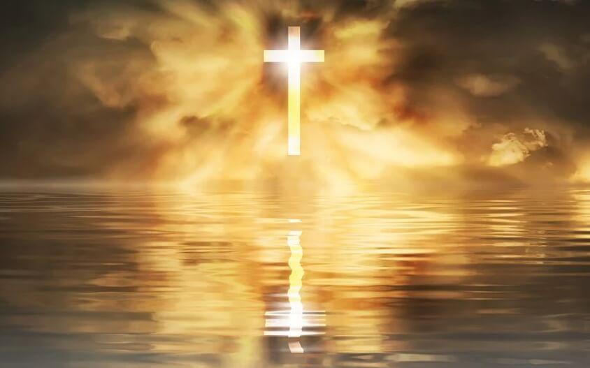 На фото изображен крест, отражающийся в воде.